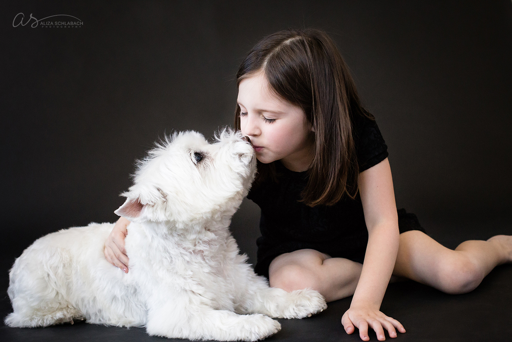 Little girl kissing her white dog