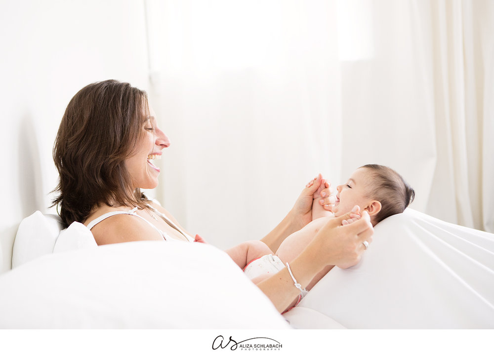 White photo of a laughing mother playing with her baby on a bed