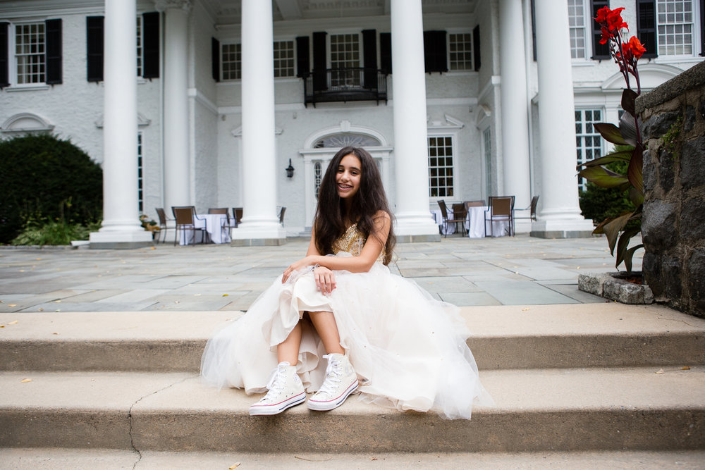 Photograph of Bat Mitzvah girl in white gown showing off her converse sneakers in front of country club