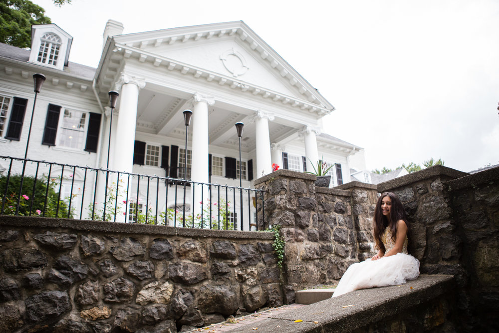 Photo of bat mitzvah girl in white gown in front of old white columned building