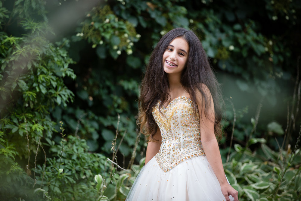Photo of smiling bat mitzvah girl in strapless gown in front of greenery