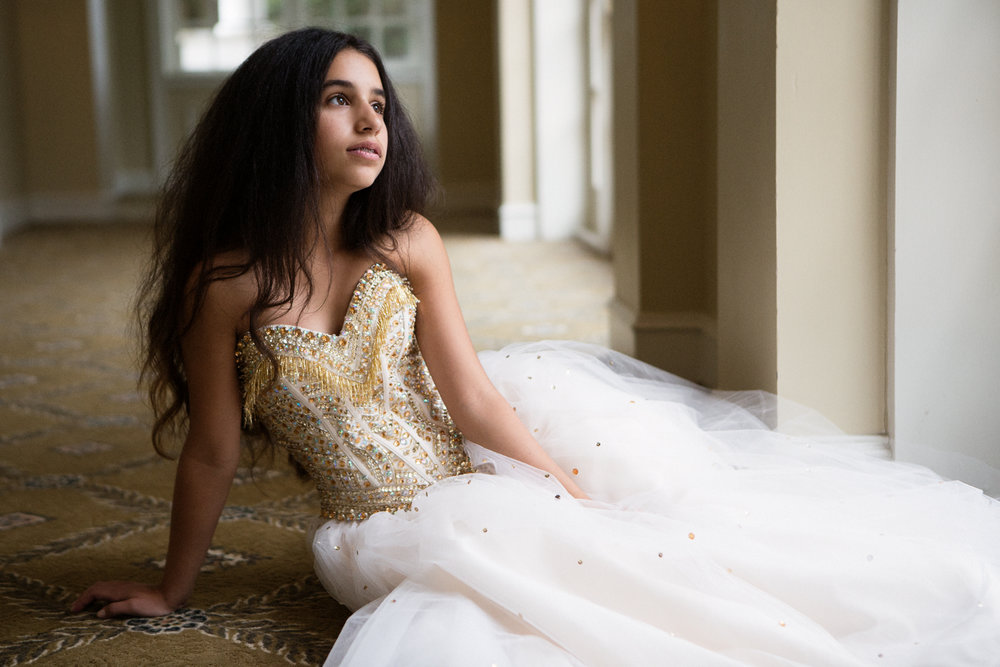 Portrait of bat mitzvah girl with long dark hair in gold and white strapless gown
