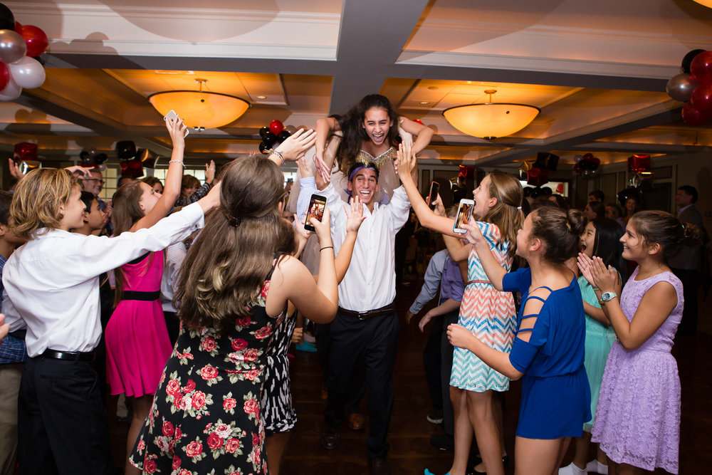 Photo of girl being carried into hall at Bat Mitzvah party