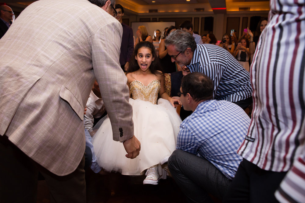 Photo of bat mitzvah girl about to be lifted during hora dance