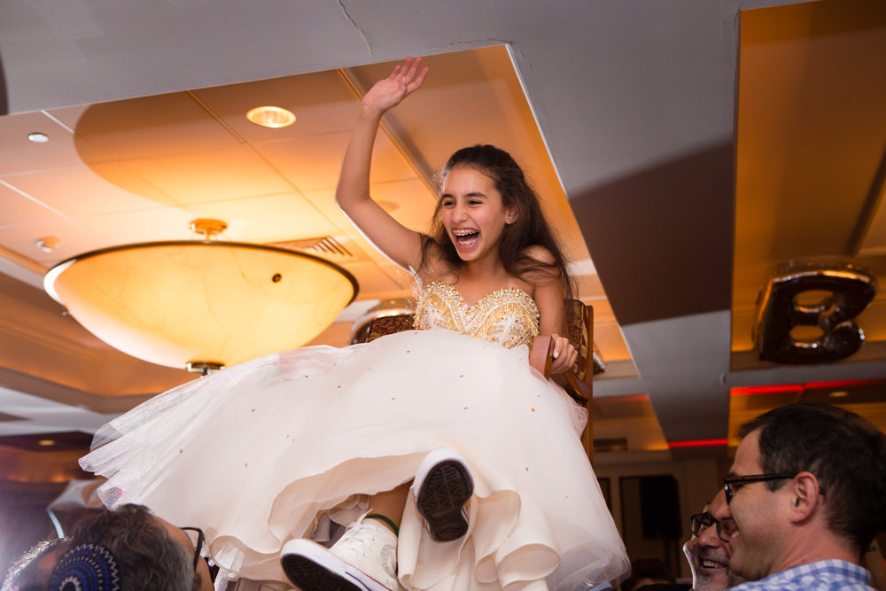 Photo of bat mitzvah girl laughing on chair during hora dance