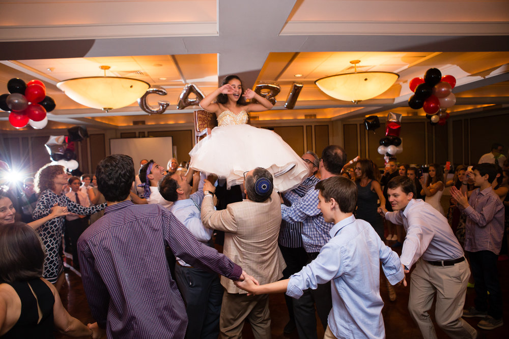 Photo of crowd dancing the hora and bat mitzvah girl on the chair