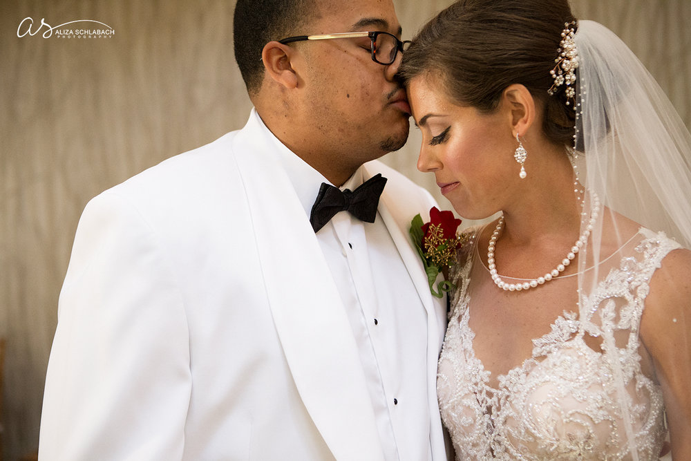 Photo of groom kissing his bride's forehead. Interracial couple.