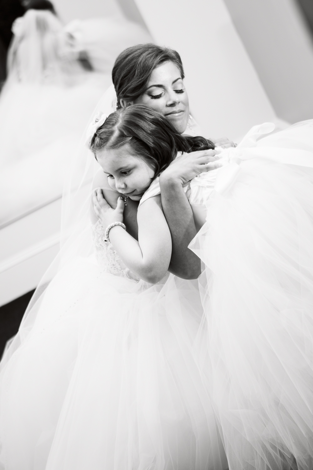 Black and white photo of bride hugging the flower girl