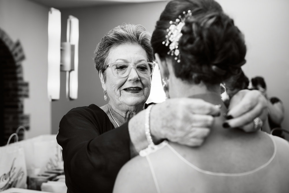 Black and white photo of mother putting necklace on her daughter, the bride.