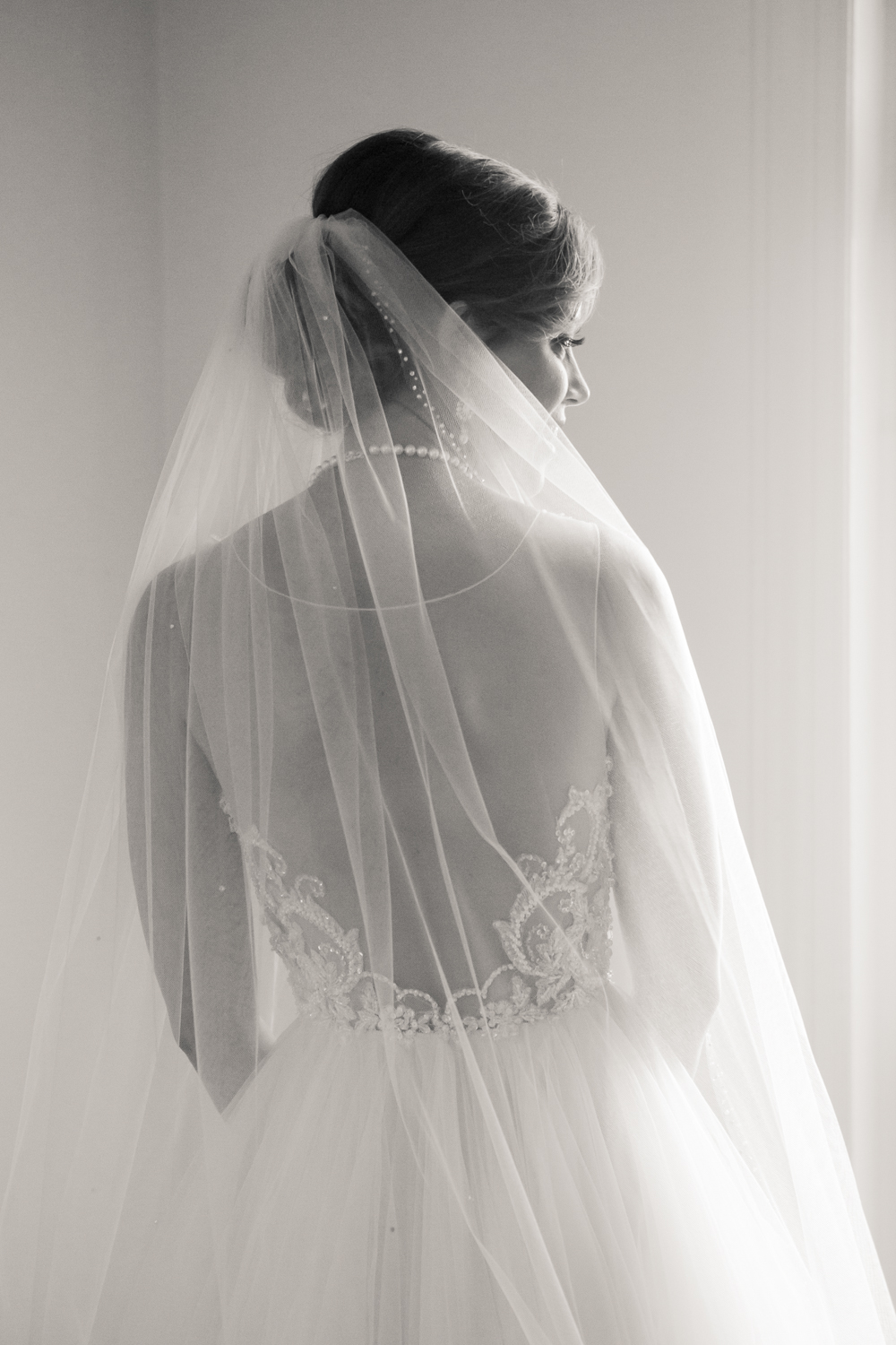 Black and white portrait of bride, back through sheer dress and veil