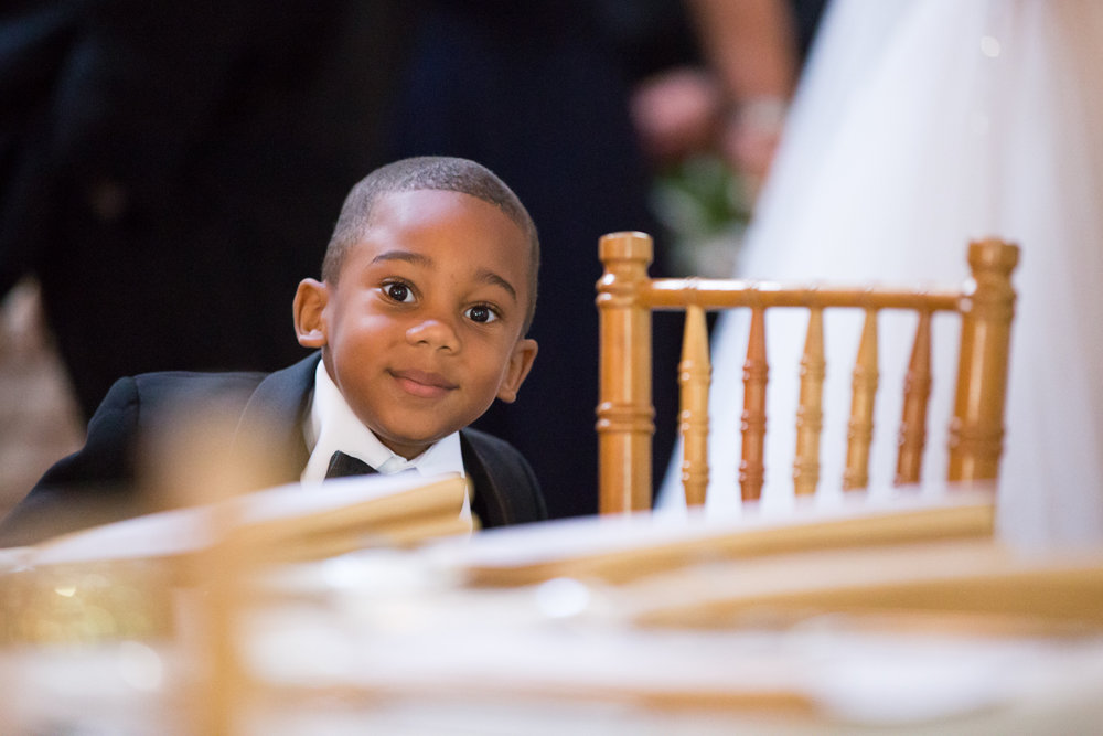 Photo of little boy in a tux at wedding reception
