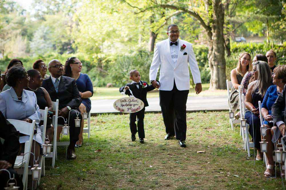 Photo of groom walking down aisle with the ring bearer at outdoor ceremony