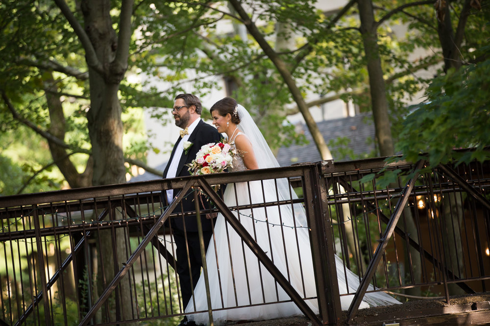 Photo of bride being walked down aisle on the bridge at The Pomme in Radnor