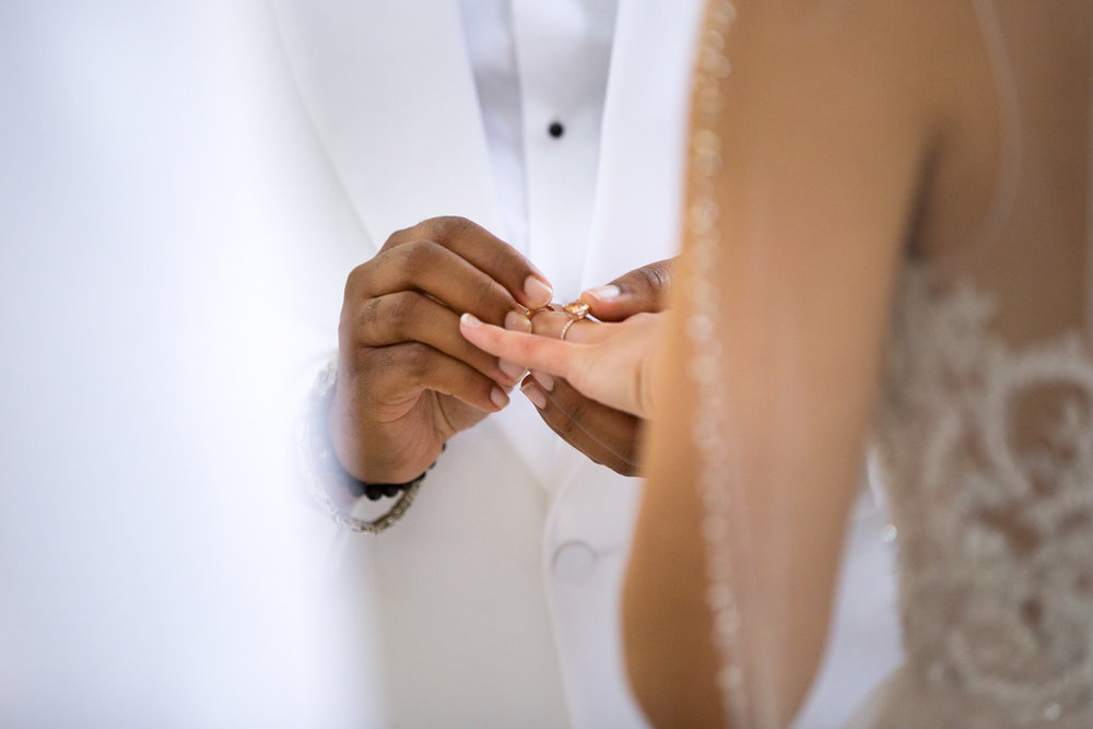 Photograph of groom's hands placing ring on bride's finger
