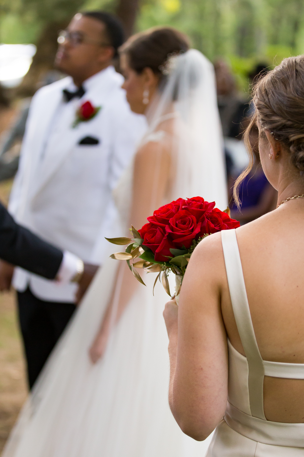 Photo of bridesmaid holding red rose bouquet with bride and groom in the background