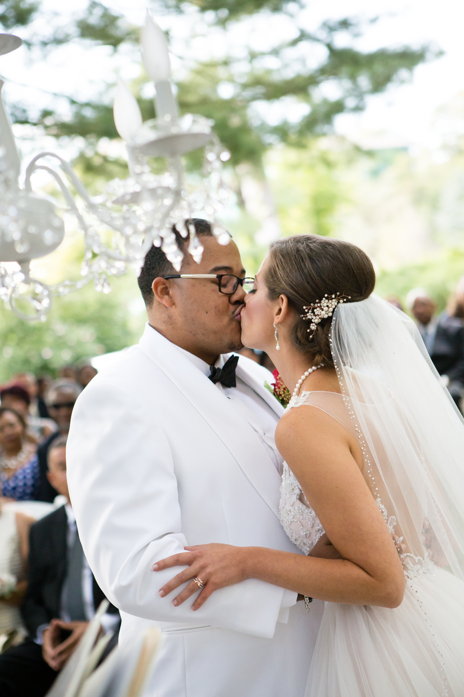 Photo of bride and groom kiss under chandelier in outdoor wedding ceremony