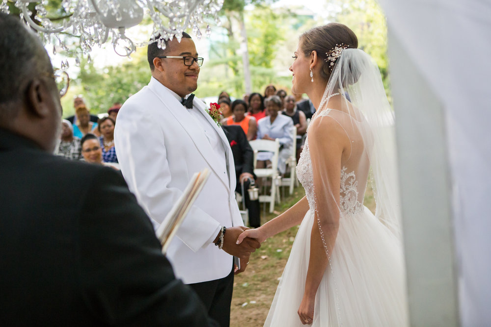 Photo of black groom and white bride during outdoor ceremony