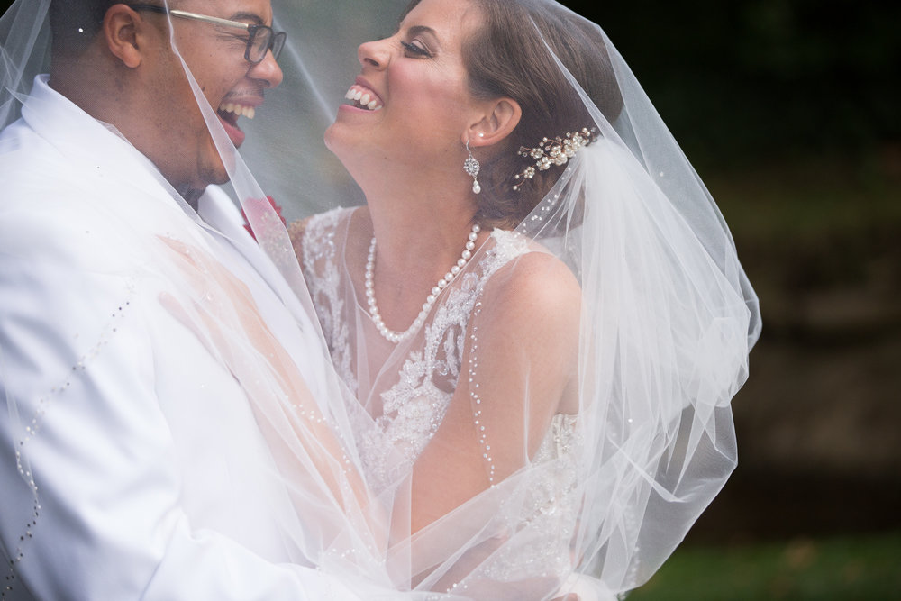 Portrait of bride and groom laughing under veil
