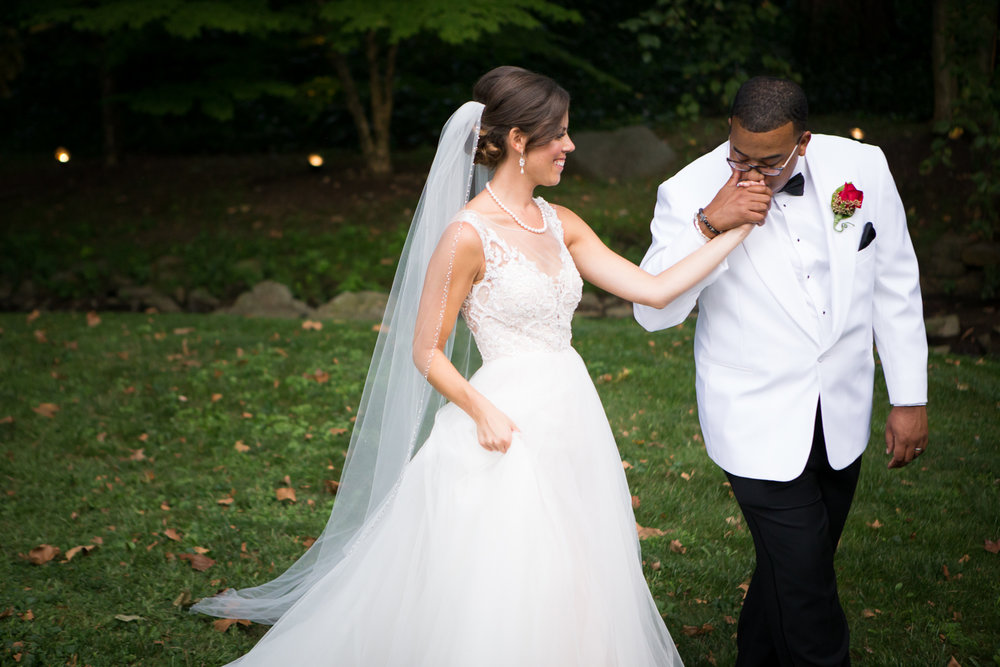 Photo of bride in white tux jacket kissing bride's hand