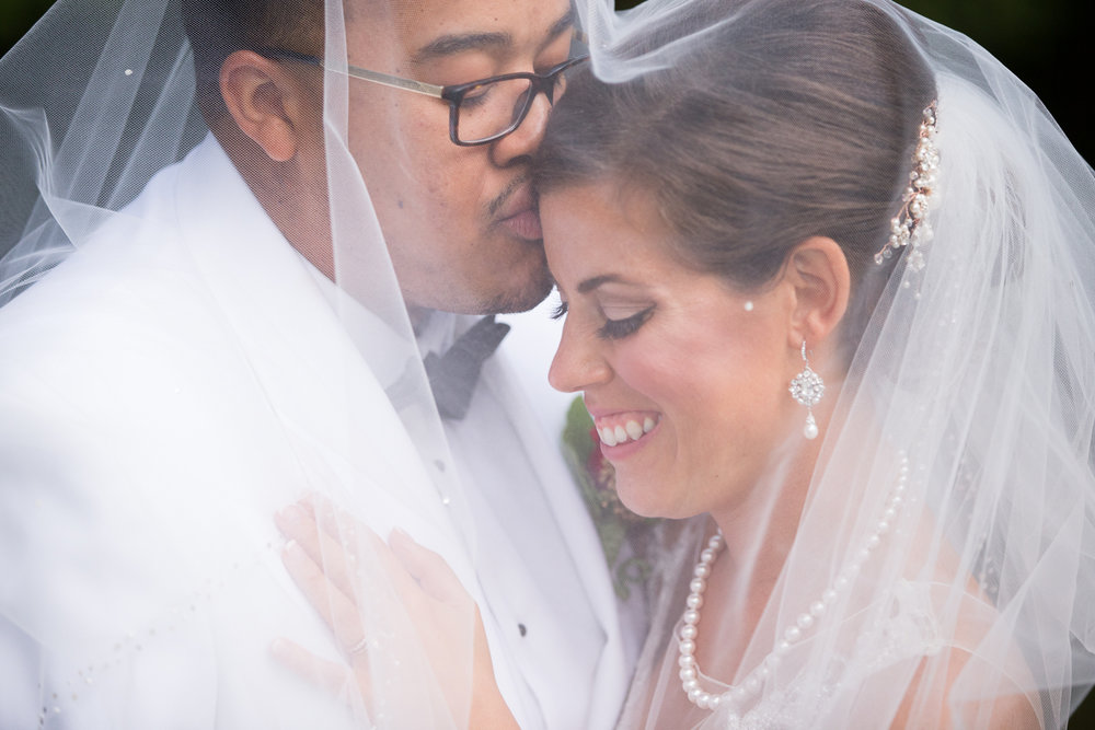 Groom kissing bride's forehead under wedding veil