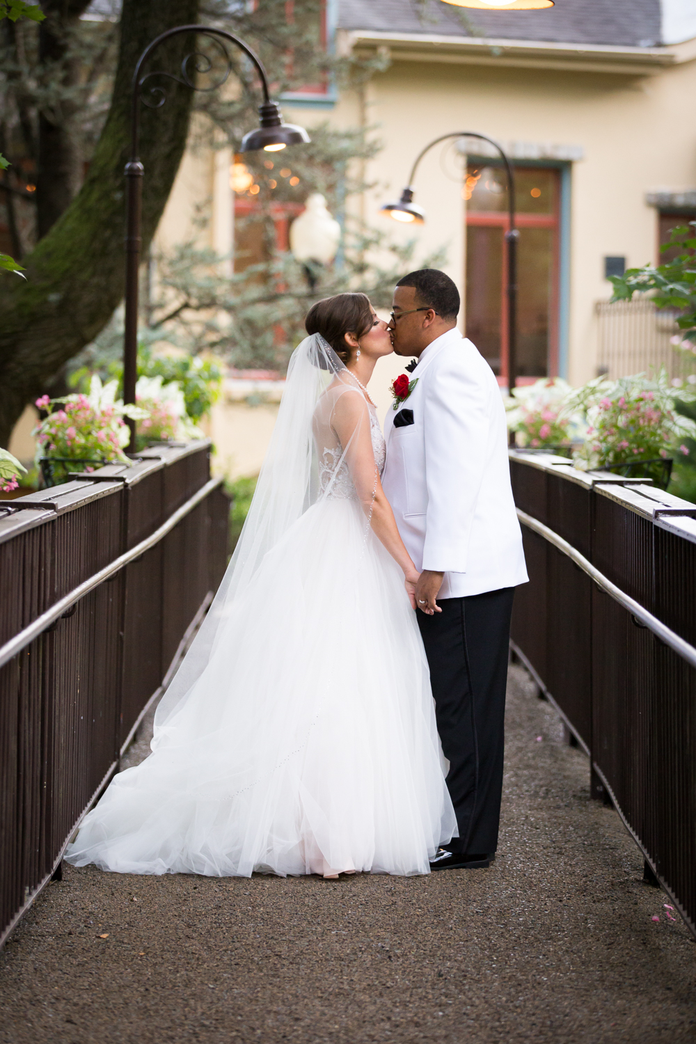 Portrait of bride and groom kissing on the bridge at The Pomme in Radnor