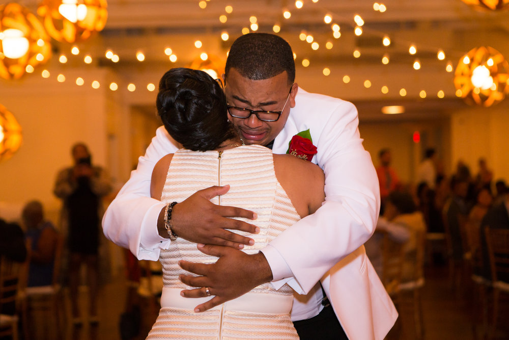 Photo of groom crying during mother son dance at wedding reception