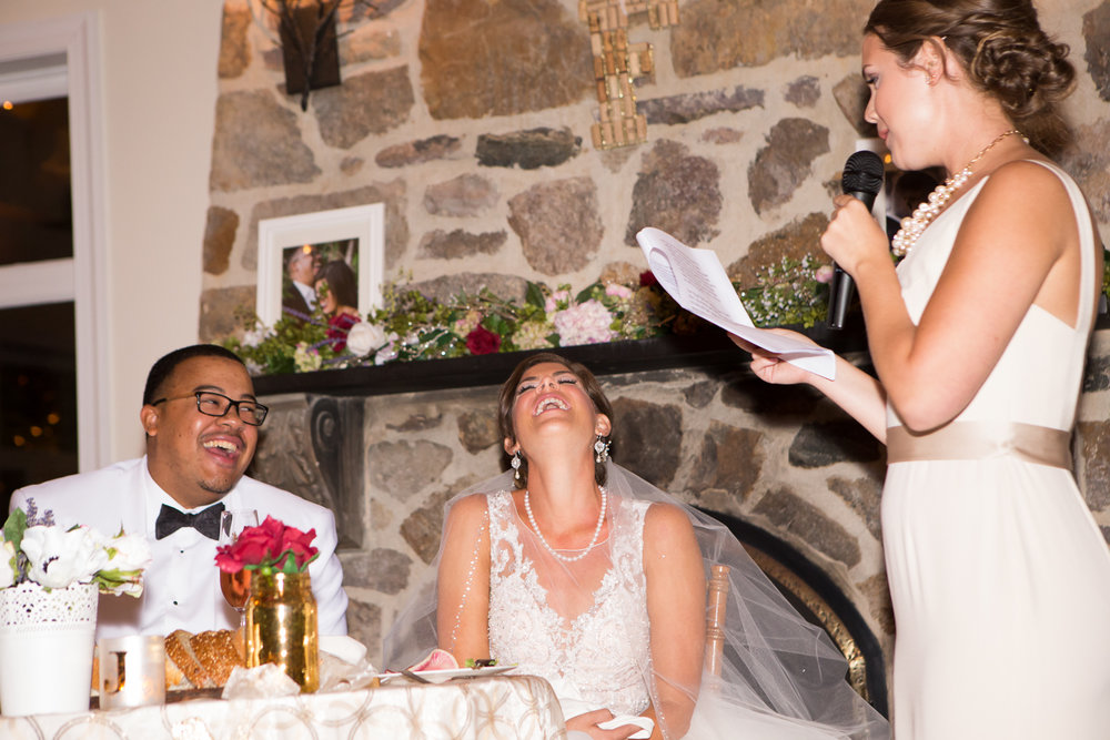 Picture of bride and groom laughing during maid of honor's speech