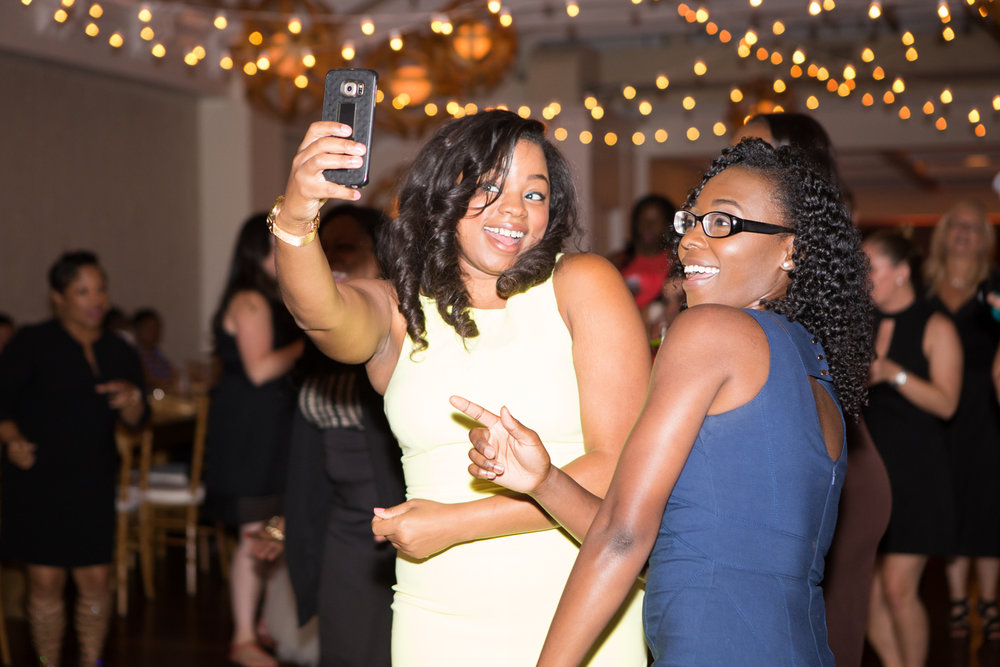 Photo of two black women taking a selfie at wedding reception