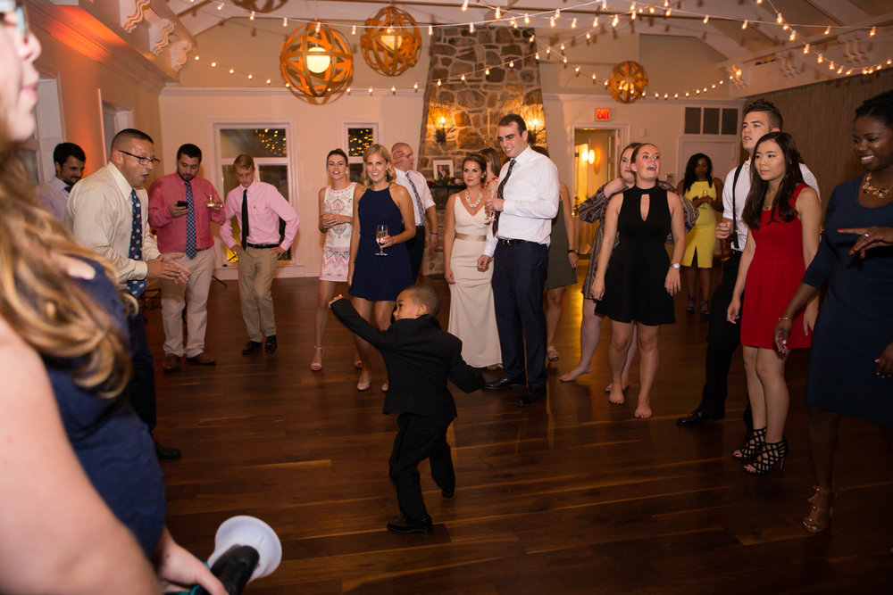 Photo of little boy dancing surrounded by adults at wedding reception
