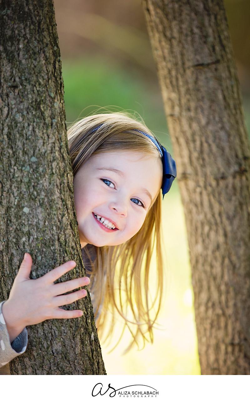 Photo of a child peering around a tree