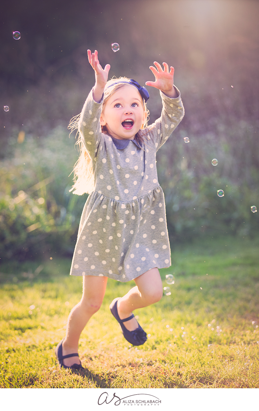 Photo of a little girl trying to catch bubbles