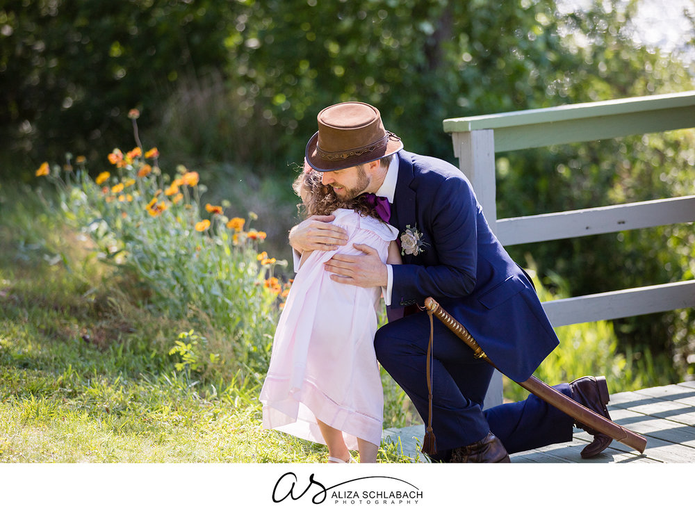 Photo of groom hugging a flower girl during his wedding ceremony
