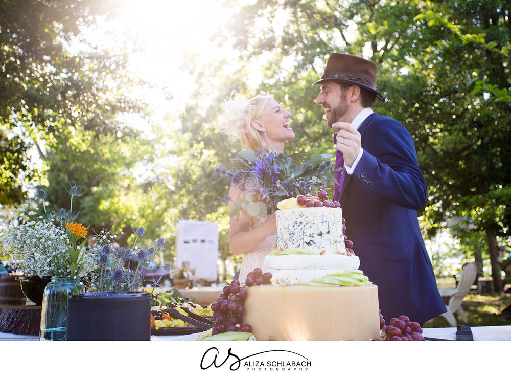 Backlit photo of bride and groom behind their wedding cake make of wheels of cheese