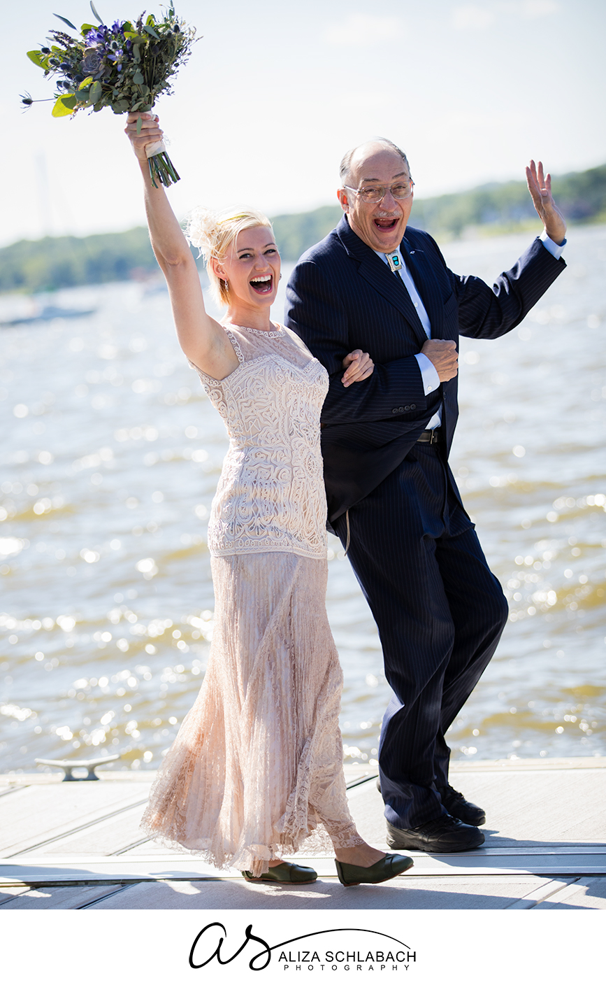 Photo of a bride and her father walking down a boat dock