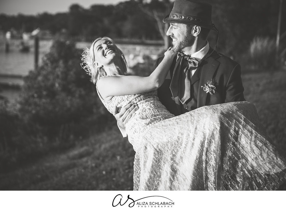 Black and white photo of a groom carrying his laughing bride