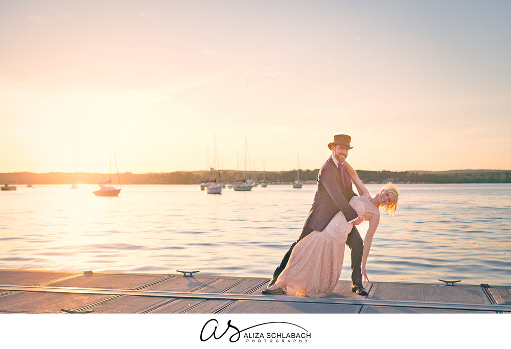 Photo of Groom in a tophat dipping his bride at sunset over the bay with sailboats