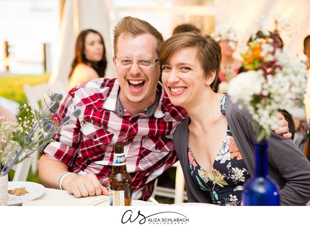 Photo of 2 laughing guests at a wedding reception in a tent