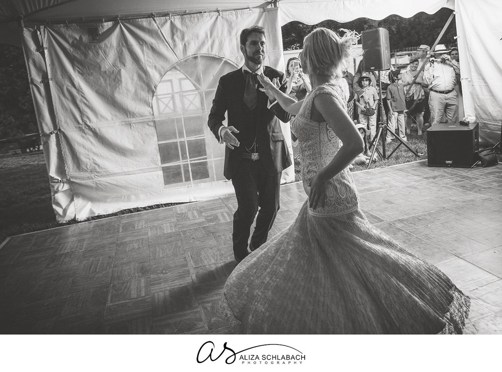 Black and white photograph of groom twirling his bride during first dance at their wedding