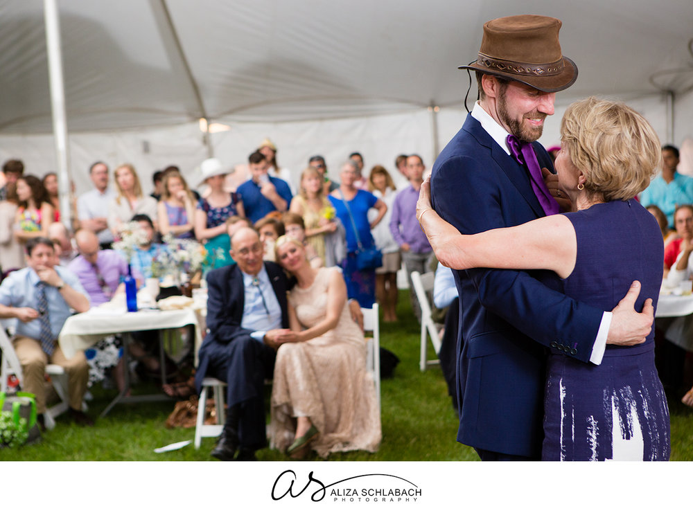 Photo of groom dancing with his mother in a tent at his wedding