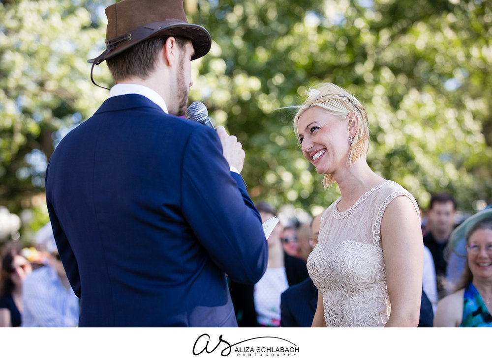 Photo of a blonde bride smiling at her groom while he speaks his vows into a microphone