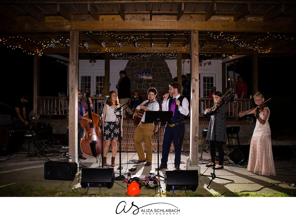 Backlit photo of bride and groom joining band during wedding reception
