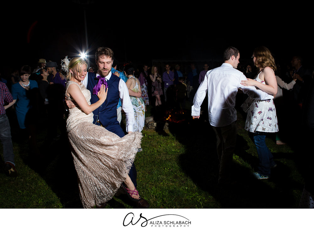 Photograph of bride and groom dancing outside at night during reception