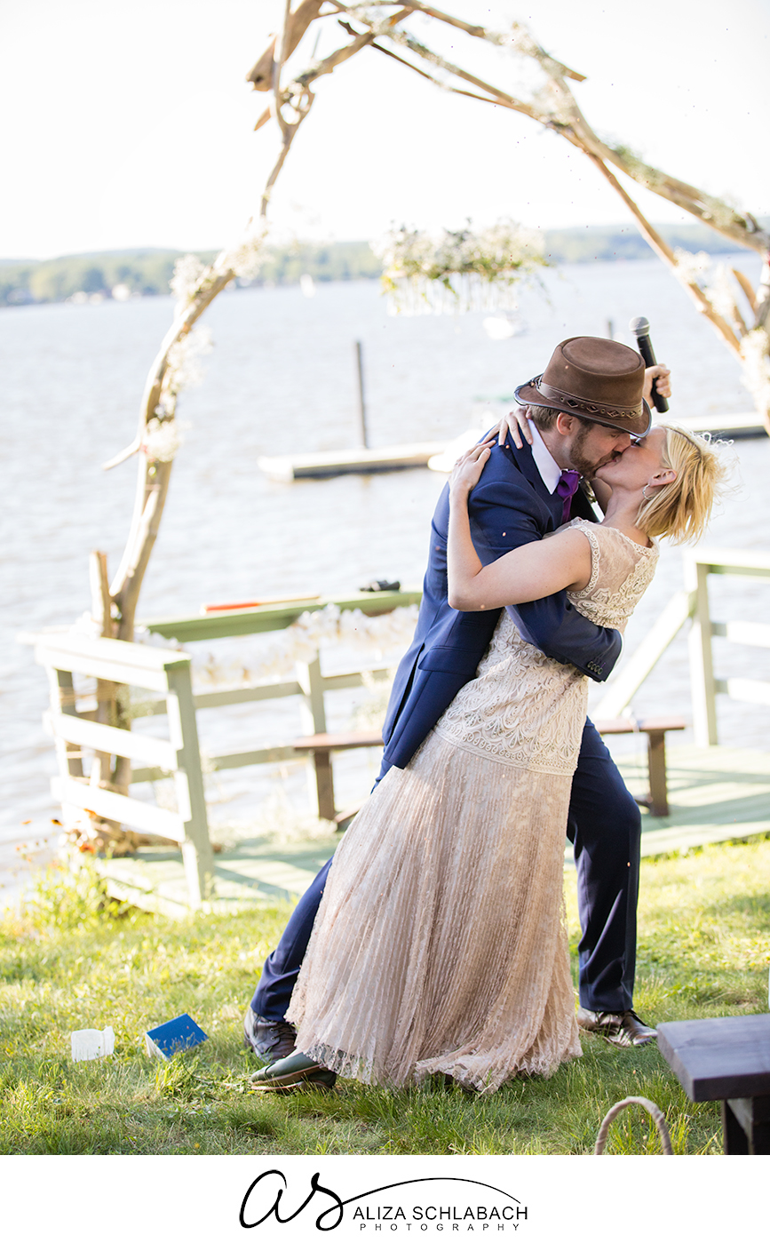 Photo of groom kissing and dipping his bride by the water