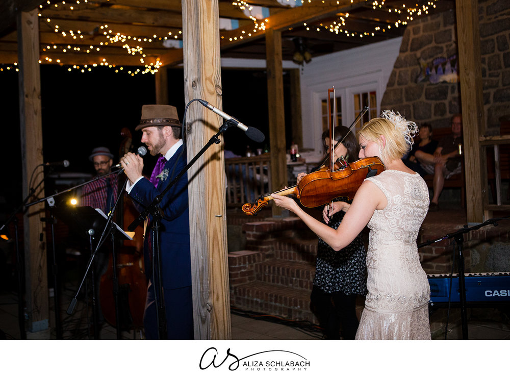 Photo of groom singing and bride playing viola during outdoor wedding reception