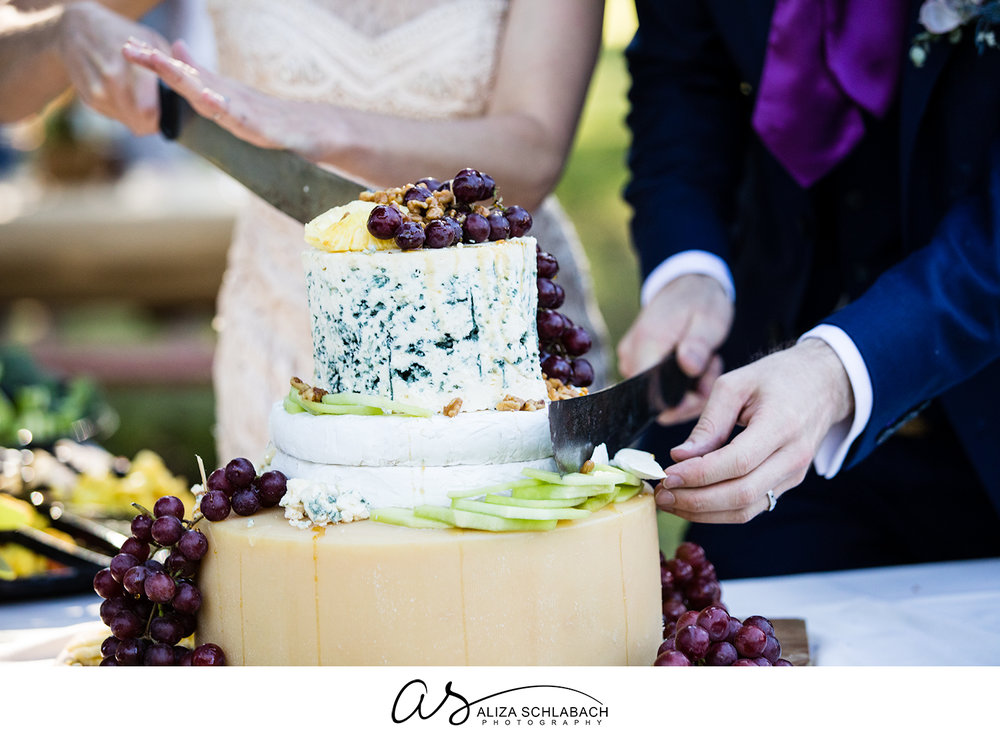 Close up photograph of bride and groom cutting their wedding cake, which is made of wheels of cheese
