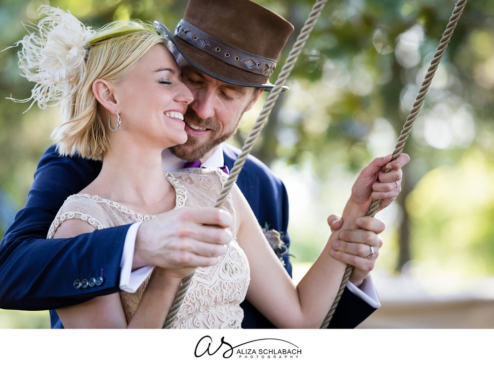 Photo of bride and groom on an outdoor wooden swing