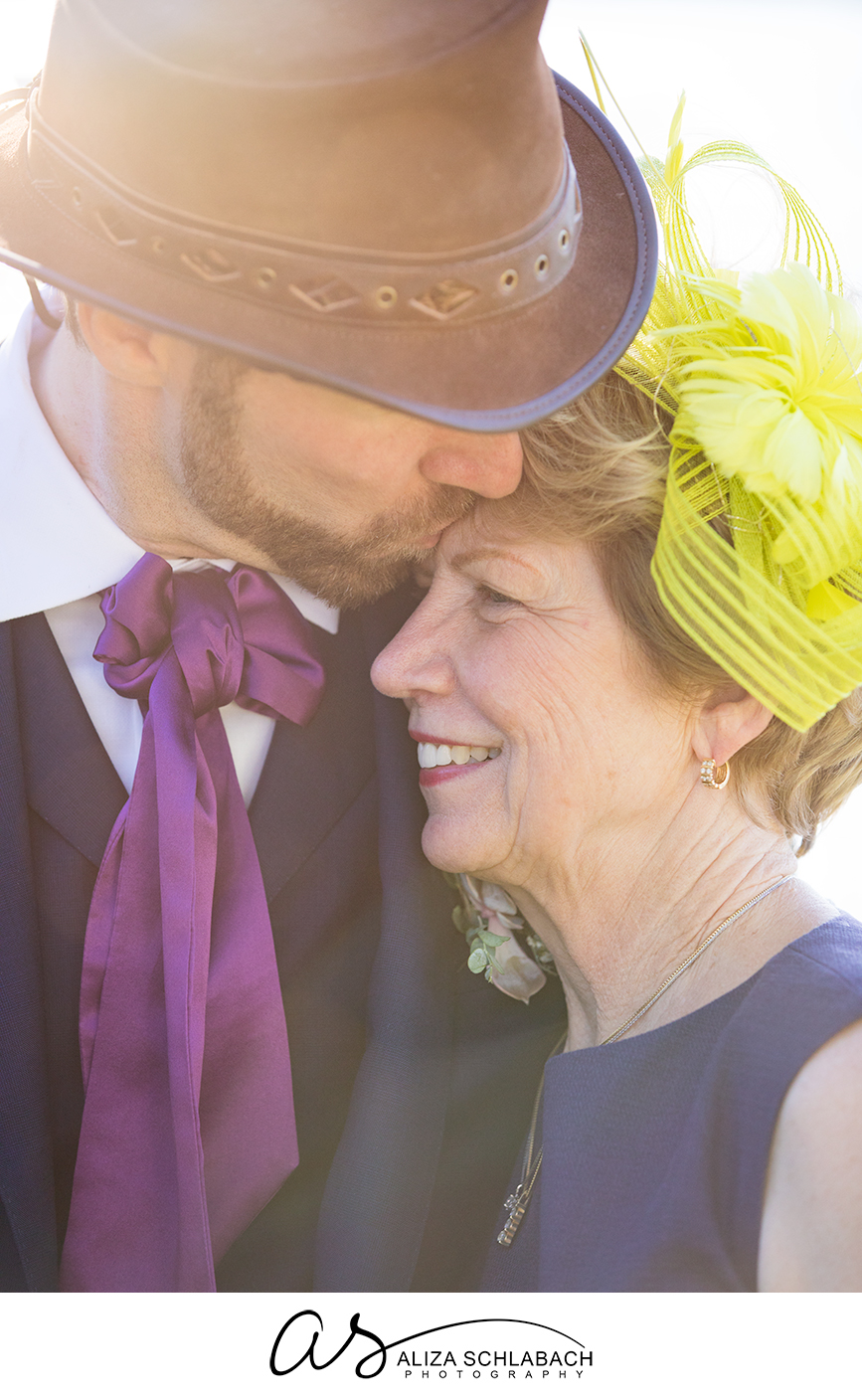 Backlit photograph of groom in hat kissing his mother's forehead