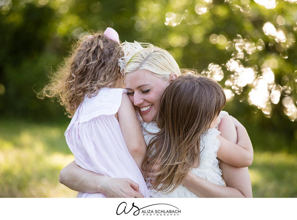 Photograph of bride hugging her flower girls outside