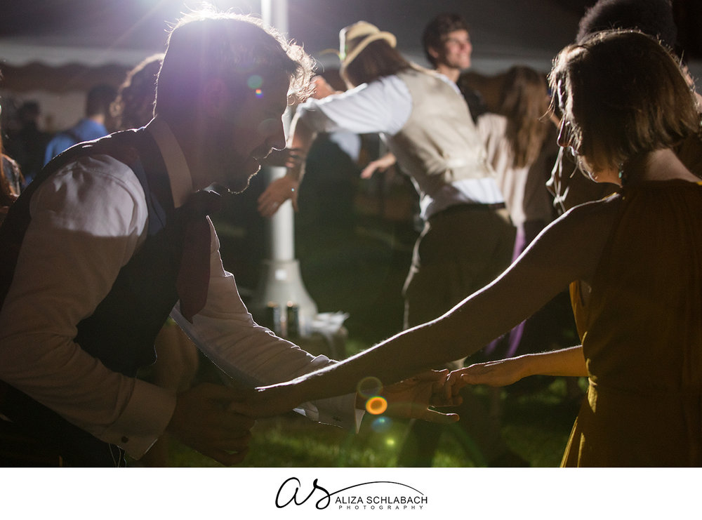 Image of groom and guest dancing during outdoor wedding reception