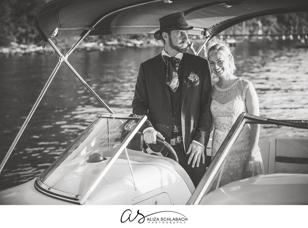 Black and white photograph of a bride and groom on a boat after their wedding